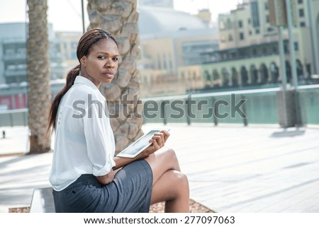 Businesswoman on coffee breaks. African businesswoman businessman holding tablet in hand while sitting on a bench and looking at the camera #277097063