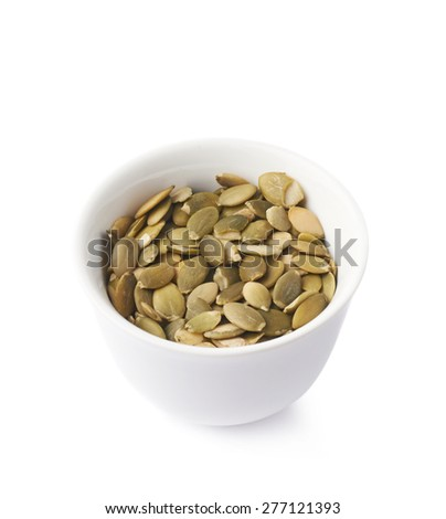 White ceramic cup bowl filled with multiple pumpkin seed snacks, composition isolated over the white background #277121393