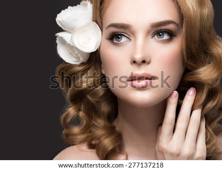 Portrait of a beautiful woman in the image of the bride with flowers in her hair. Picture taken in the studio on a black background. Beauty face
