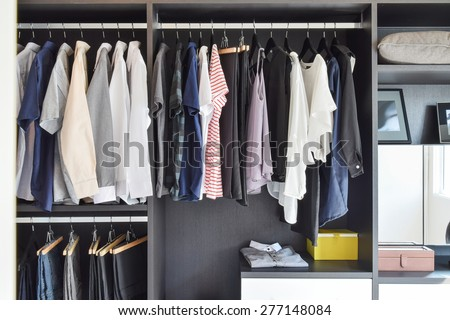 modern closet with row of cloths hanging in black wardrobe #277148084
