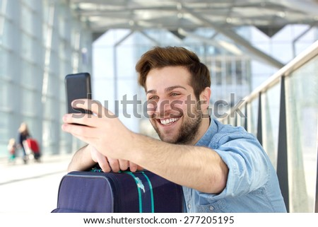 Portrait of a young man laughing and taking selfie #277205195
