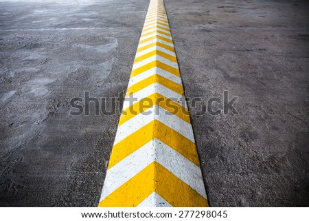 A yellow stripe speed ramp on concrete road. #277298045