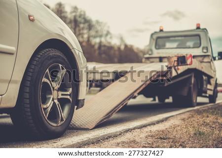 Loading broken car on a tow truck on a roadside  #277327427