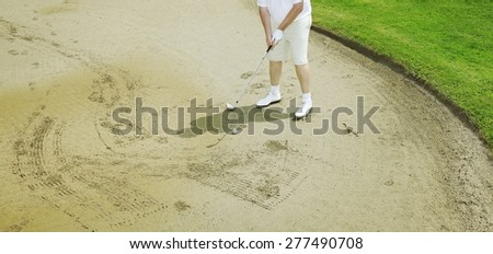 Picture of a man golfing in the sand.