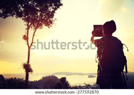 young woman hiker taking photo with digital tablet #277592870