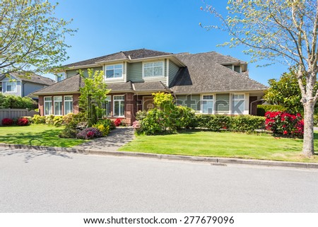 Custom built luxury house with nicely trimmed and designed front yard, lawn in a residential neighborhood in Canada. #277679096