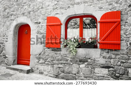 Old stone house with red wooden shutters and red door. Boxes with red and white flowers on the window. Brittany, France. Retro aged photo.  #277693430
