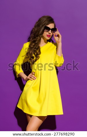 Fashion Model Posing On a Violet Background. Beautiful girl in sunglasses posing in yellow mini dress. Three quarter length studio shot on purple background. #277698290