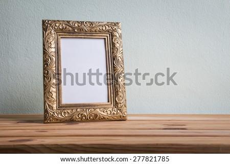 Vintage photo frame on wooden table over grunge background