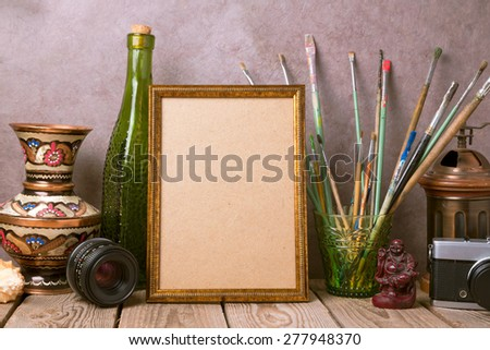 Mock up poster frame with vintage artistic objects and old camera on wooden table