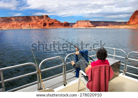 Woman relaxes and enjoys the fantastic views of sandstone cliffs and blue skies.  She is on a houseboat on Lake Powell in Arizona.  She fishes holding the rod with her toes. #278020910