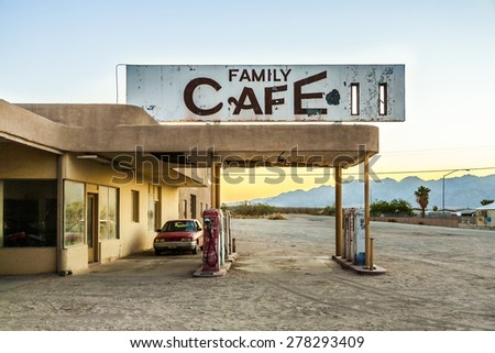 wrecked car at an abandoned petrol station in the desert village of Desert Center in sunset Royalty-Free Stock Photo #278293409