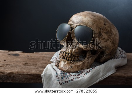 still life photography : skull wearing sunglasses with bohemian pattern handkerchief on old wood with sullen background