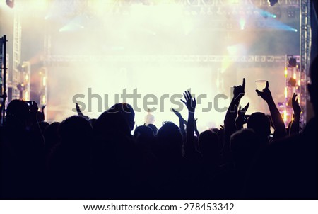 Cheering crowd in front of bright colorful stage lights - retro styled photo  #278453342