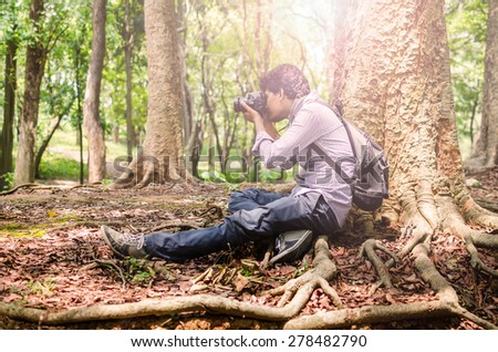 Photographer taking photos sitting under a big tree using digital SLR camera in natural outdoor, vintage look