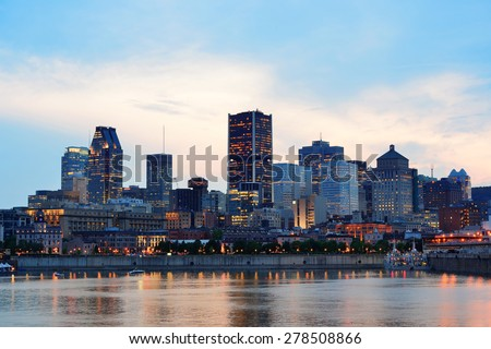 Montreal over river at sunset with city lights and urban buildings