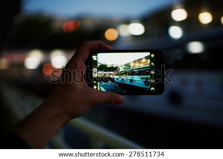 Person taking a photo of touristic sail boat using smart phone camera,male hand holding cell phone while taking a photograph of night lights city in travel,taking a picture of outdoors,blur background