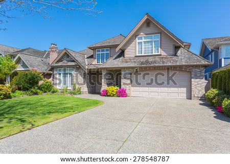 Luxury house with nicely trimmed and designed front yard, lawn in a residential neighbourhood in Canada. #278548787