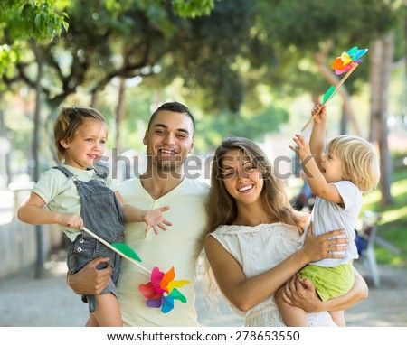 Cheerful young parents holding kids with toy windmills at summer day #278653550