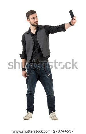 Young smiling bearded hipster taking selfie from high angle. Full body length portrait isolated over white background.