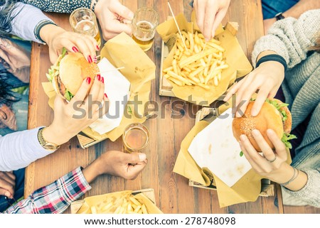 Group of friends toasting beer glasses and eating at fast food - Happy people partying and eating in home garden - Young active adults in a picnic area with burgers and drinks #278748098