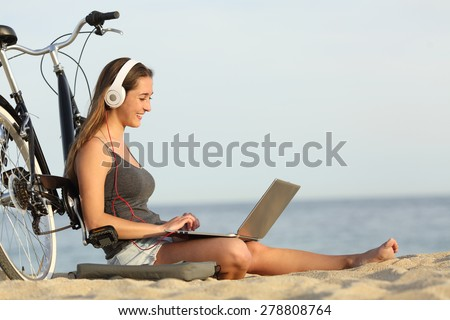 Teen girl studying with a laptop on the beach leaning on a bicycle Royalty-Free Stock Photo #278808764