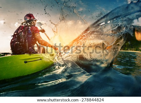Young lady paddling hard the kayak with lots of splashes Royalty-Free Stock Photo #278844824