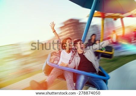 Beautiful, young couple having fun at an amusement park #278874050