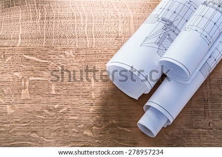 Rolls of blueprints on wooden oaken board construction concept  Royalty-Free Stock Photo #278957234