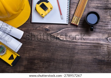 Copybook pencil cup of coffee and construction objects on pine wood board maintenance concept  #278957267