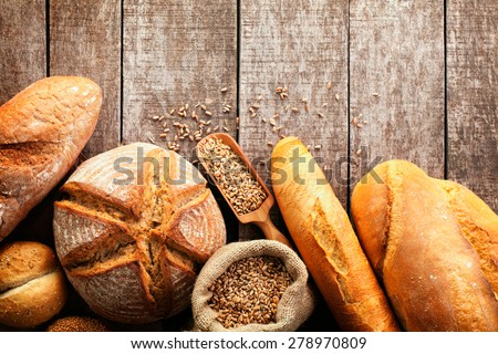 Assortment of baked bread on wooden table background Royalty-Free Stock Photo #278970809
