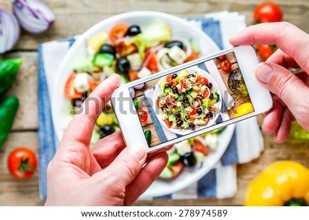 Smartphone taking picture from organic greek salad