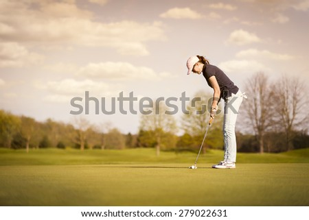 Woman golf player putting on green at dusk, with empty copyspace. #279022631