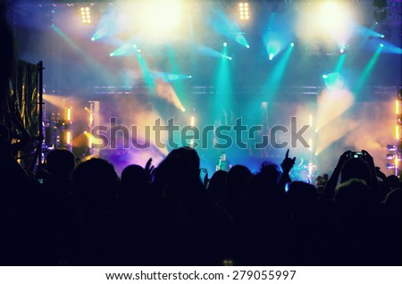 Cheering crowd in front of bright colorful stage lights - retro styled photo #279055997