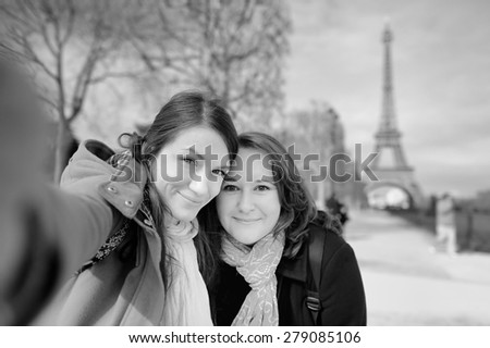 Black and white photo of two young woman taking a self portrait (selfie) near the Eiffel tower  #279085106