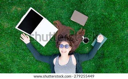 portrait of a beautiful brunette student girl with laptop computer and books on the green grass in the park in spring time. #279255449