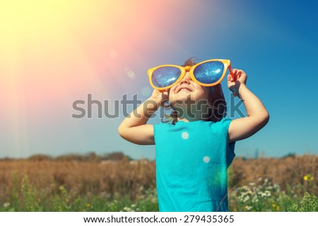 Happy little girl with big sunglasses walking in the meadow and looking at the sun Royalty-Free Stock Photo #279435365
