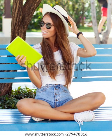 closeup of happy woman in glasses using tablet pc in the park Young woman wearing summer sunglasses denim shorts,travel hat,soft photo,travel concept,laptop,seeing internet online,straw hat,accessory #279478316