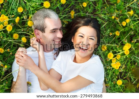 Young loving couple lying at the green grass with dandelion in the park park   #279493868