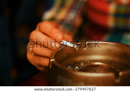 Woman smoking cigarette and using an ashtray, cigarette in an ashtray #279497627