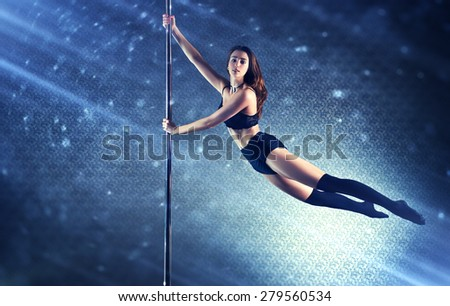 Young slim pole dance woman flying on pole. Special light rays and spots motion effect. #279560534