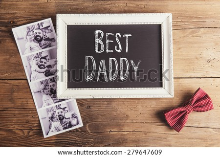 Picture frame with Best daddy sign, instant photos and bow tie on wooden background.
