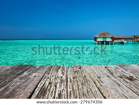 Beautiful beach with water bungalows and old wooden pier at Maldives #279674306