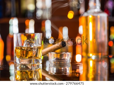 Whiskey drink with smoking cigar on bar counter #279766475
