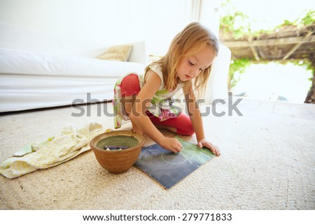 Shot of innocent little caucasian girl sitting on floor coloring a picture with color chalks. Schoolgirl drawing at home #279771833