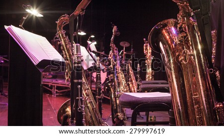 Saxophone section. A break in rehearsals for the horn section of a big band. Royalty-Free Stock Photo #279997619