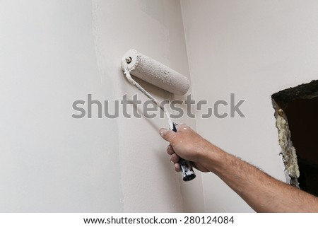 Man's hand painting a wall using paint roller. #280124084