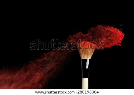 powderbrush on black background with red powder splash close up #280198004