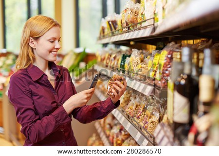 Young woman scanning barcode of bag of nuts in supermarket with her smartphone