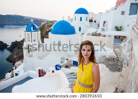 Walking tourists. Beautiful feminine woman on the streets of the old Greek town of Oia. Santorini, Greece.  #280392650